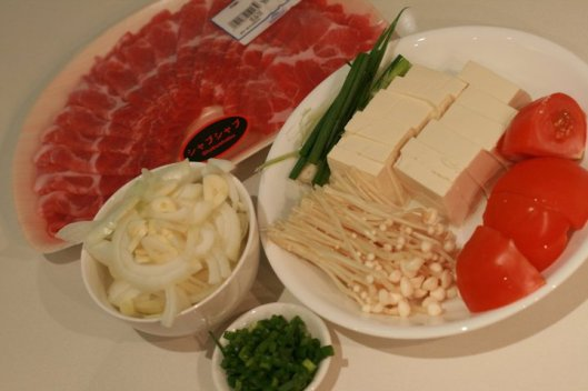 Kimchi jiggae ingredients: Onions and garlic, tofu, pork slices, spring onions, enoki mushrooms, kimchi, tomatoes and milk